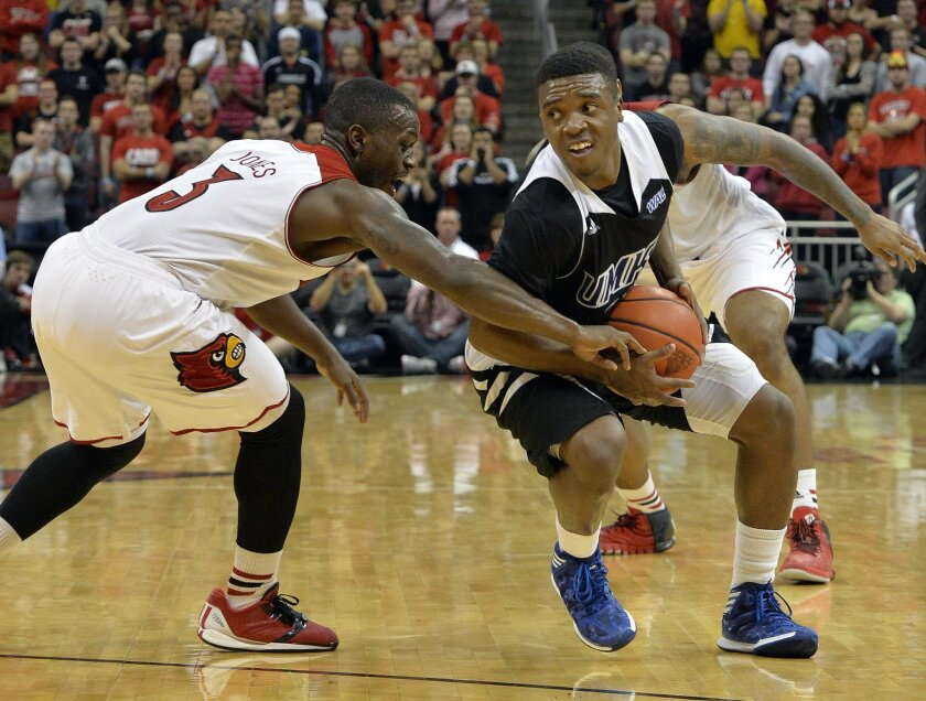 Louisville's Chris Jones, left, attempts to steal the ball away from Missouri-Kansas City's Martez Harrison during the first half of an NCAA college basketball game on Wednesday, Dec. 4, 2013, in Louisville, Ky. (AP Photo/Timothy D. Easley)
