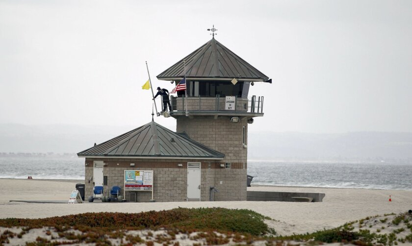 On the day after the Boston bombing, flags were brought down to half staff in Coronado. Coronado Lifeguard Damon Bassett lowers the flags on the main tower, including the US flag to half staff in honor of those killed in Boston Monday.