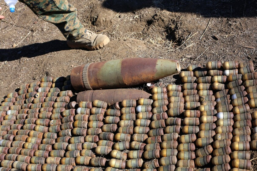 A grenade round that was 'dropped, kicked, or bumped' caused an explosion among these 350 grenade rounds and two larger shells, killing four Marines during a Nov. 13 training exercise at Camp Pendleton. The fatal explosion occurred just minutes after this picture was taken. The grenades and shells were being collected from an impact area for disposal.
