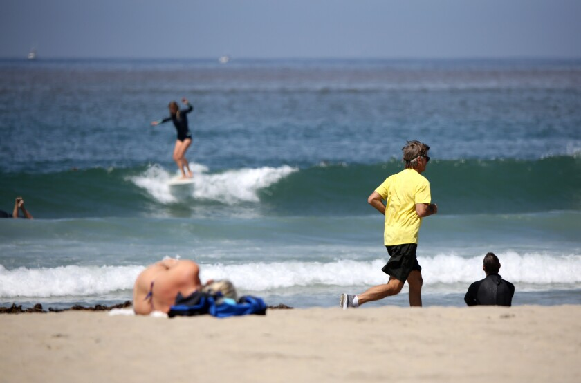 One day after Newport Beach opened up its beaches to recreational activities, surfers and joggers took to the shore at the Newport Pier in Newport Beach on Thursday.