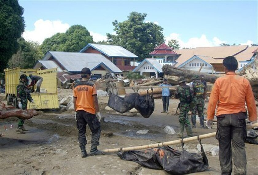 Rescuers carry the bodies of flash flood victims in Wasior, Papua province, Indonesia, Wednesday, Oct. 6, 2010. Heavy rain unleashed flash floods and mudslides in the remote corner of the country, sweeping away residents in a fast-moving wall of sludge, rocks and heavy logs and leaving thigh-high water in its wake. (AP Photo/Abdul Muin)