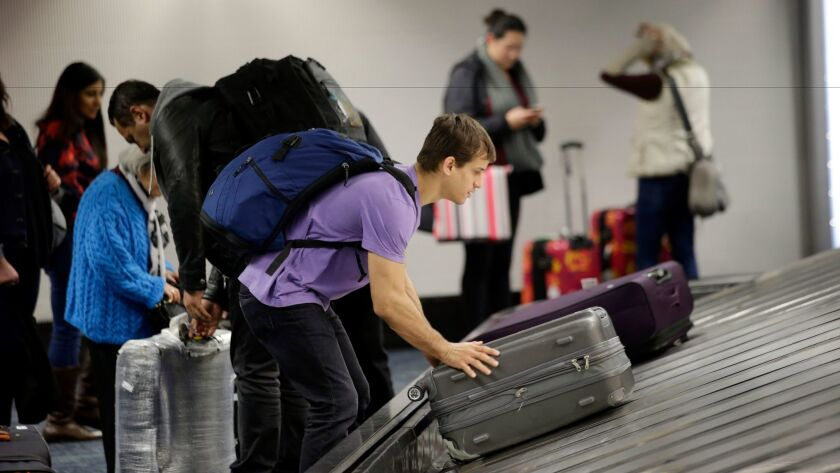 A traveler gathers his luggage at San Francisco International Airport. U.S.-based airlines reported the lowest rate of lost or mishandled luggage since the data were first collected in 1987.