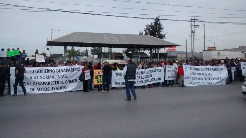 Several hundred protestors opposed to Mexican customs fees for importing used U.S. vehicles blocked southbound commercial traffic crossing into Mexico at Otay Mesa on Monday.