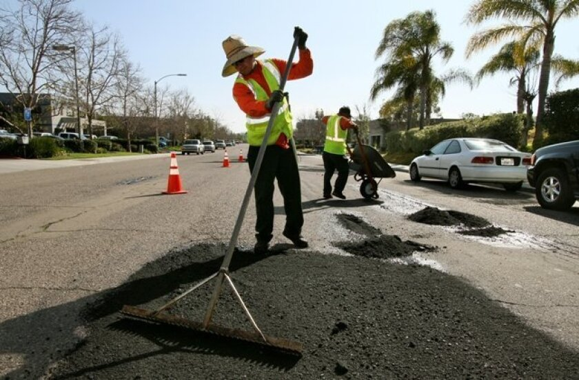 Daniel Saavedra smoothed out fresh asphalt as he and other employees of George W. Weir Asphalt Construction filled potholes along Corporate Drive in Escondido. UT File Photo