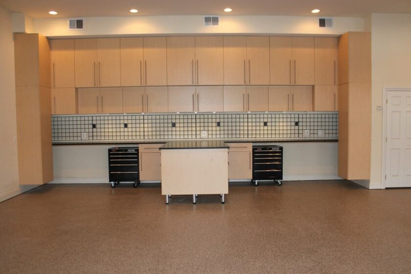 In this 2012 photo provided by Tailored Living/Premier Garage, a 4-car garage is seen after being transformed into a useful and more attractive space. More and more owners are turning to professionals to help them renovate their garages. Advances in flooring and storage products make it easier than