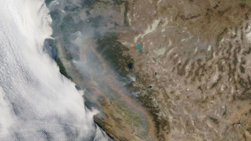 Smoke from the Northern California fires drifts over land and sea in a view taken from space on Tuesday.