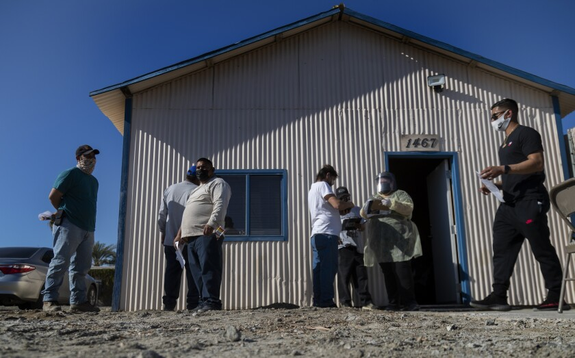 Farmworkers arrive at a site to receive a COVID-19 vaccine.