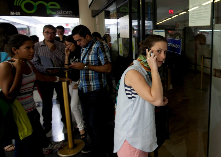 A woman speaks on her phone as she seeks information about flight sales outside a closed United Airlines office in Caracas, Venezuela. Some airlines have suspended ticket sales transacted in bolivars, the local currency, until the government pays money it owes the carriers.