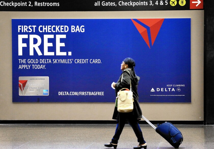 Delta Air Lines' privacy policy shows what consumers are up against when trying to figure out how their personal info will be used. Above, a traveler walks past a sign advertising a Delta credit card at Seattle-Tacoma International Airport in SeaTac, Wash.