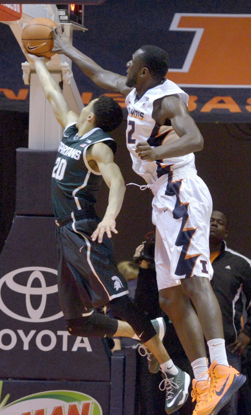 Illinois' forward/center Nnanna Egwu, right, rejects a shot by Michigan State's guard Travis Trice (20) during an NCAA college basketball game in Champaign, ILL on Sunday, Feb. 22, 2015. (AP Photo/Robin Scholz)