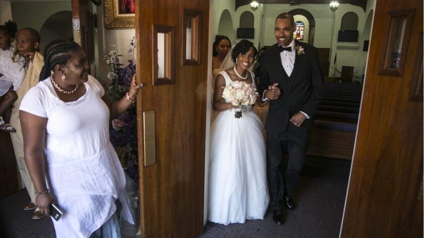 Jamie Nieto and his bride, Shevon, walk together after marrying at the Greater Christ Temple Apostolic Church.