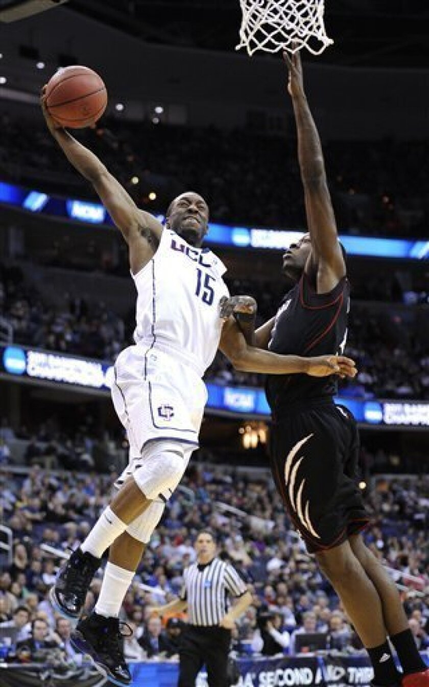 Connecticut guard Kemba Walker (15) heads toward the basket as Cincinnati forward Justin Jackson reaches to block the shot during the first half of the West Regional third-round NCAA tournament college basketball game, Saturday, March 19, 2011, at the Verizon Center in Washington. (AP Photo/Nick Wass)