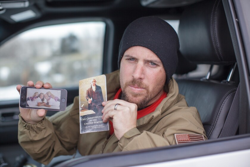 Jon Ritzheimer shows a family picture on his phone and a copy of a pocket Constitution at the Malheur National Wildlife Refuge Headquarters near Burns, Ore.