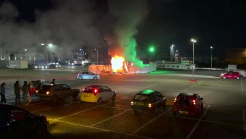 A structure is on fire at night in a lighted parking lot