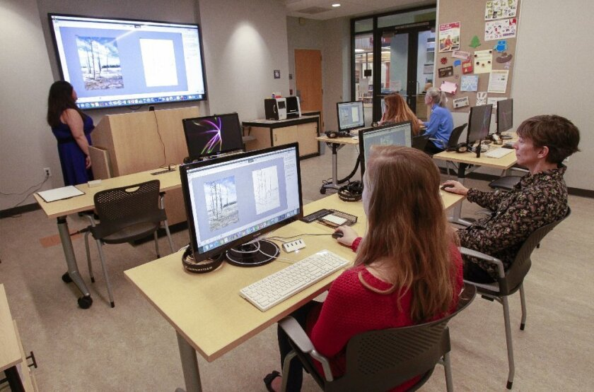 Librarian Maile McKeon, back left, teaches a group on how to work on photos using Adobe Photoshop Elements at the Dove Library in Carlsbad on Tuesday