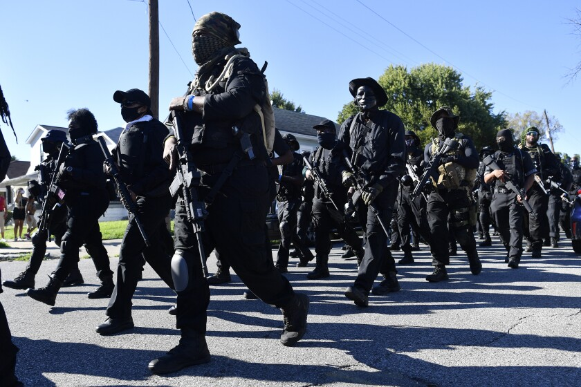 Members of the NFAC, a Black militia, march to Churchill Downs racetrack before the 146th running of the Kentucky Derby, in Louisville, Ky., Saturday, Sept. 5, 2020. (AP Photo/Timothy D. Easley)