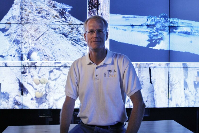 Falko Kuester, a professor of computer science and visualization at UC San Diego, sits in front of screens that show some of the Bermuda shipwrecks that his team is digitizing with high resolution cameras.