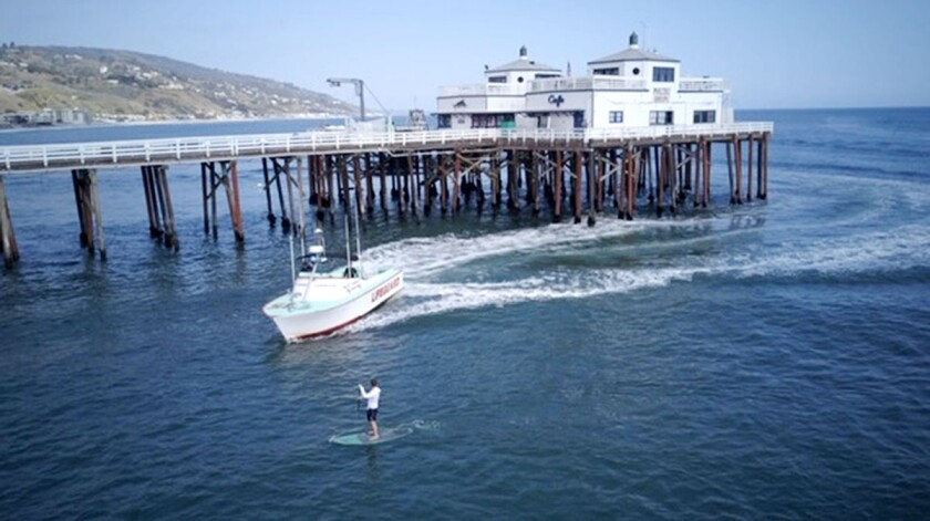 A man paddle boarding near the Malibu Pier was arrested Thursday after authorities said he disobeyed lifeguards and violated a statewide stay-at-home order amid the coronavirus pandemic.