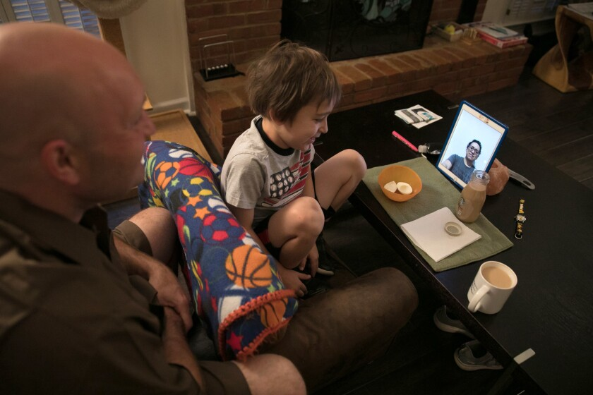 Jason Rochester and his son Ashton Rochester, 6, Face Time with his wife Cecilia Rochester in Mexico