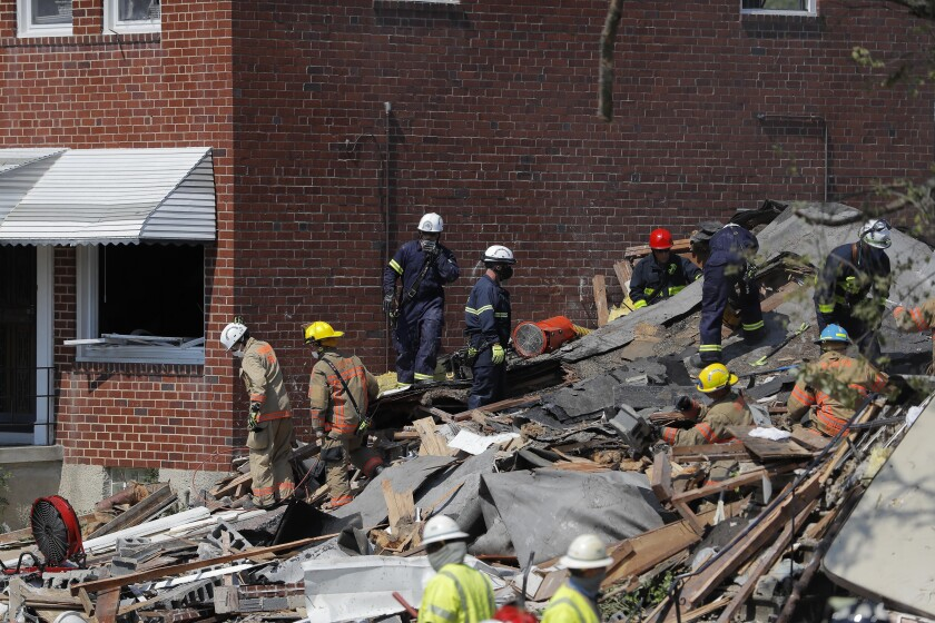 "Authorities walk among the piles of debris from an explosion in Baltimore on Monday, Aug. 10, 2020. The ""major gas explosion"" that involved three houses at Labyrinth and Reistertown roads has left multiple people, including children, trapped according to the Baltimore Fire Department. (AP Photo/Julio Cortez)"