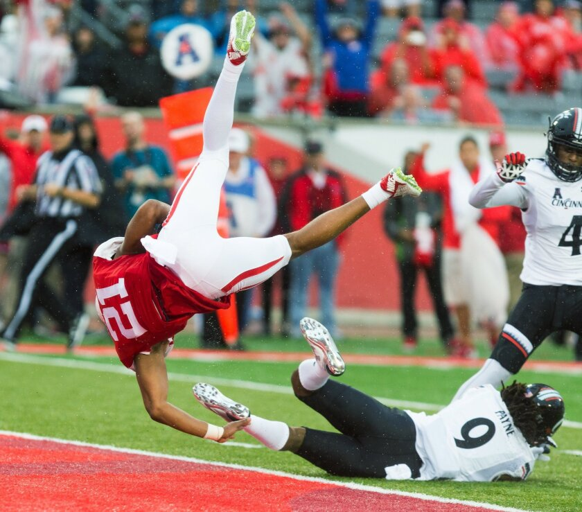 Houston's Ralph Harvey Jr. flips into the end zone scoring after being hit by Cincinnati's Leviticus Payne (9) during the first half of an NCAA college football game at TDECU Stadium, Saturday, Nov. 7, 2015, in Houston. (AP Photo/Juan DeLeon)
