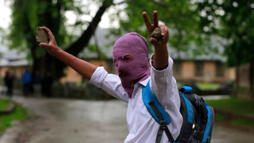 A masked Kashmiri student holds stones during clashes outside Kashmir Polytechnic College in Srinaga
