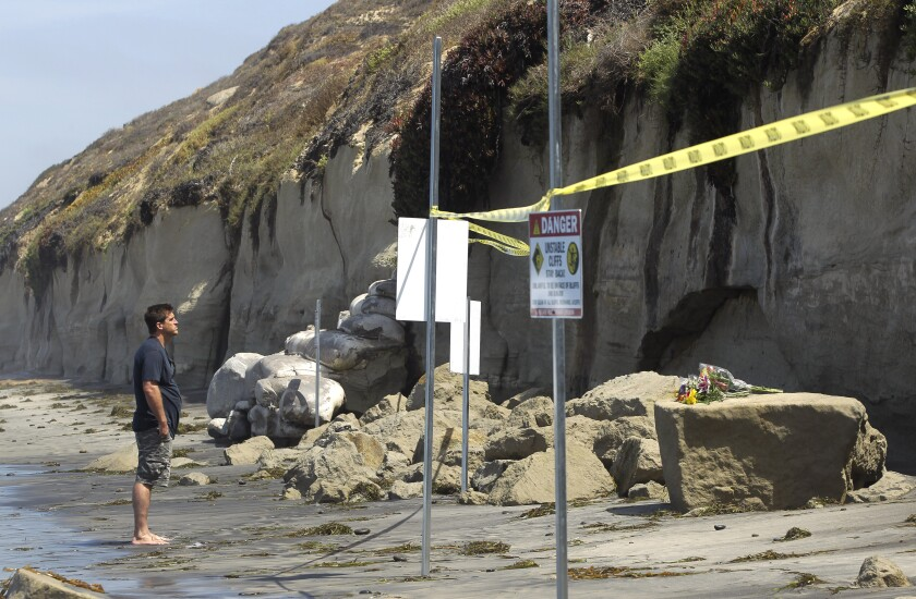A man looks at looks at the debris left from the fatal bluff collapse last August at Grandview Beach in Encinitas