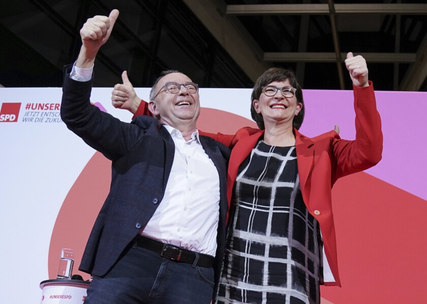 Norbert Walter-Borjans and Saskia Esken wave after the announcement of the result of the vote on the SPD chairmanship in the Willy Brandt House in Berlin, Germany, Saturday, Nov. 30, 2019. Walter-Borjans and Esken have won the vote. The new leadership will be confirmed at the party conference on December 6. (Kay Nietfeld/dpa via AP)