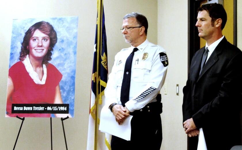Salisbury Police Chief Jerry Stokes, left, and Detective Sgt. Travis Shulenburger stand next to a picture of Reesa Trexler, who was killed in 1984, Tuesday, Dec. 3, 2019 in South. Police were able to identify Trexler's killer through DNA tests. The body of the 15-year-old Trexler was found on the floor of a bedroom in her grandparents' house in June 1984. (Shavonne Walker/The Salisbury Post via AP)