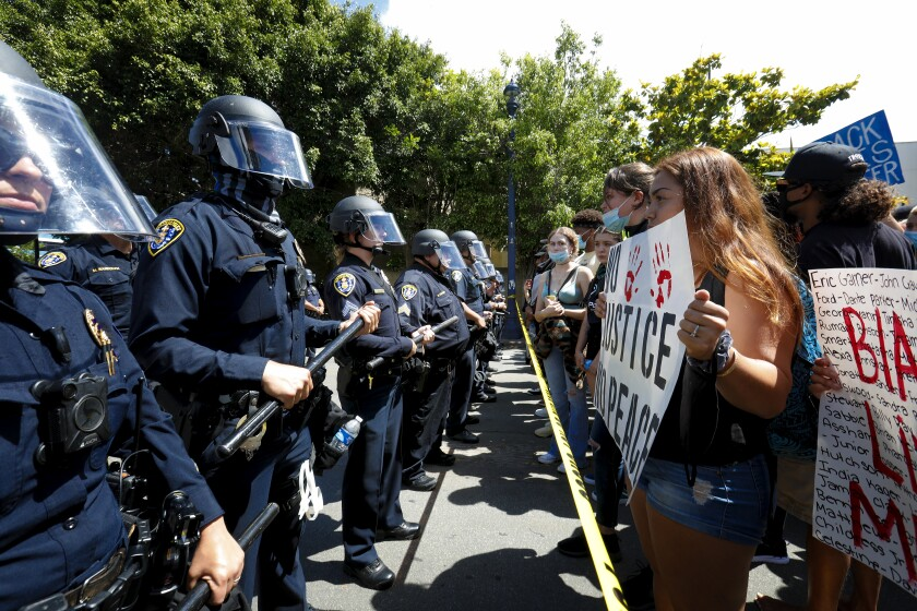 In June 6, 2020 file photo, protestors face off with officers outside the downtown San Diego Police Department headquarters.