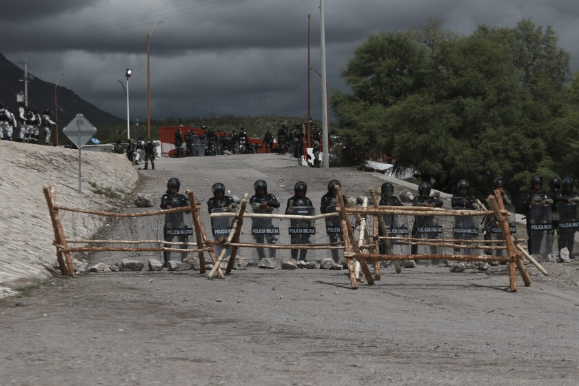Military police in helmets and riot shields stand behind a wood and barbed-wire barricade on a gravel road