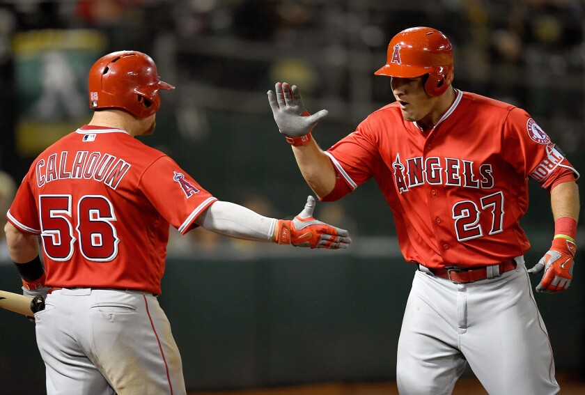 Angels outfielder Mike Trout (27) is congratulated by teammate Kole Calhoun (56) after hitting his first home run of the season.