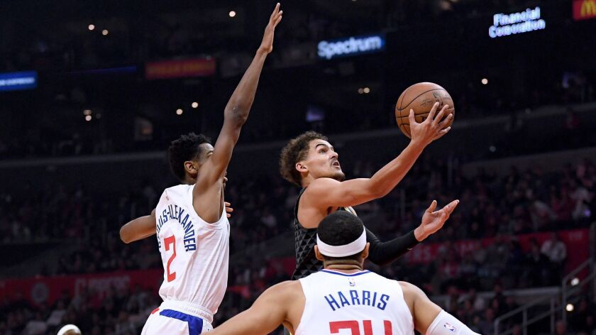 Trae Young (11) of the Atlanta Hawks scores on a layup against Shai Gilgeous-Alexander (2) and Tobias Harris (34) of the Clippers during the first half.