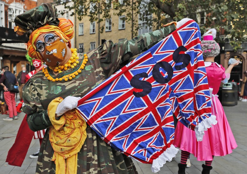 Actors dressed as pantomime dames pose for photographers before they march on Parliament to demand more support for the theatre sector amid the COVID-19 pandemic, in London, Wednesday, Sept. 30, 2020. (AP Photo/Frank Augstein)