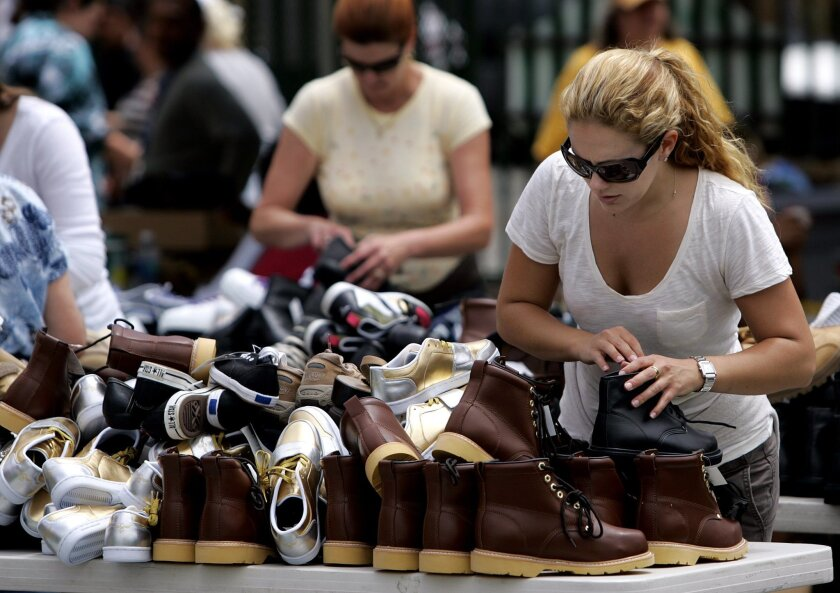 Volunteer Cacee Cobb looks through shoes at the Soles4Souls program at St. Vincent de Paul on Monday.
