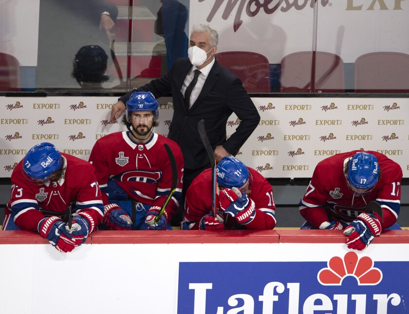Montreal Canadiens coach Dominique Ducharme watches the final seconds of the game as Tyler Toffoli (73), Phillip Danault (24), Brendan Gallagher (11) and Josh Anderson (17) sit on the bench during the third period of Game 3 against the Tampa Bay Lightning in the NHL hockey Stanley Cup Final, Friday, July 2, 2021, in Montreal. (Ryan Remiorz/The Canadian Press via AP)