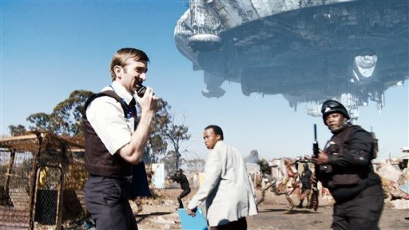 "FILE - This undated file movie still from Sony Pictures shows, left to right, Sharlto Copley, Mandla Gaduka and Kenneth Nkosi in ""District 9."" The movie, one of the summer's biggest blockbusters, a sci-fi morality tale about aliens and apartheid, is not welcome in Nigeria because of its portrayal o"