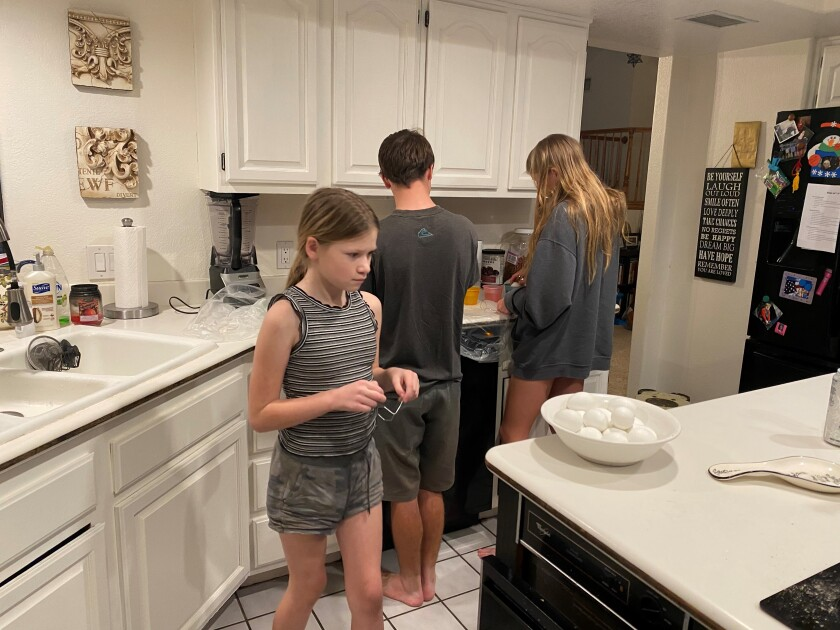 Siblings Rachel Palma, Adam Grato and Phoebe Slade enjoy their kitchen after working on its renovation.