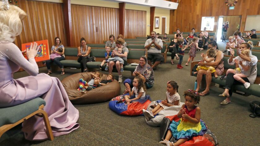 Parents and children applaud after listening to drag queen Autumn Rose, left, read children's storie