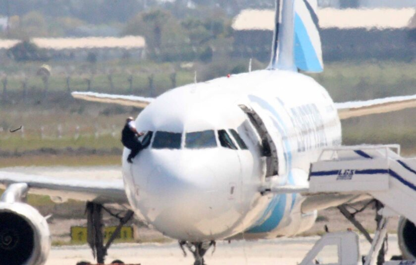 A person believed to be a member of the crew climbs out of a cockpit window of the hijacked EgyptAir A320 plane parked at a sealed off area of the Larnaca Airport, in Larnaca, Cyprus.