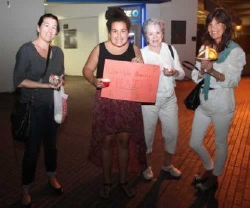 People gather in downtown La Jolla Monday night, Sept. 9 to light candles and brandish signs during a rally to promote a peaceful response to the Syrian conflict.