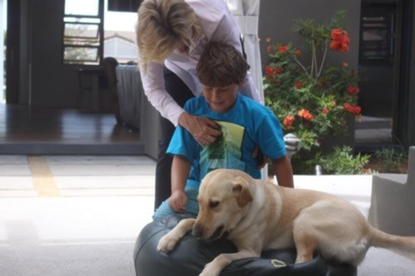 Nine-year-old Otto Lana of La Jolla gets the reassurance he needs to face busy days from his service dog, Cara,