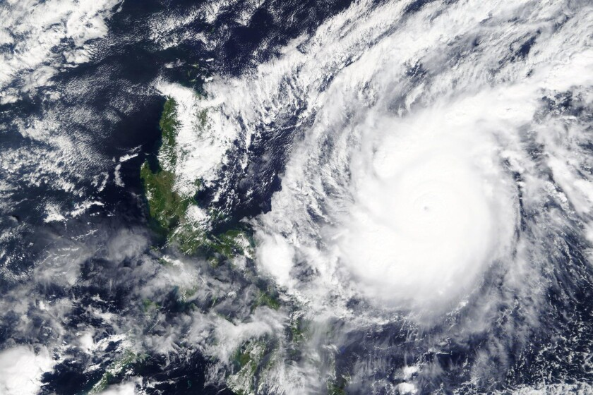 A satellite image shows the white swirl of Typhoon Goni over the ocean.