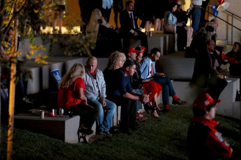 People sit outdoors at an election night watch party