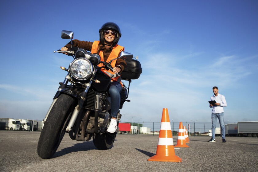 A female student takes motorcycle lessons.