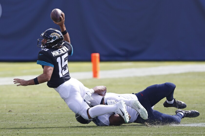 Jacksonville Jaguars quarterback Gardner Minshew (15) is sacked by Tennessee Titans defensive tackle Jack Crawford for a 20-yard loss in the first half of an NFL football game Sunday, Sept. 20, 2020, in Nashville, Tenn. (AP Photo/Wade Payne)