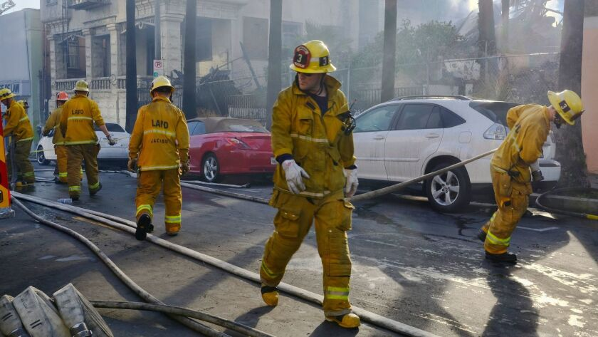 Firefighters wrap up their hoses after extinguishing a fire at a Los Angeles apartment building in April.