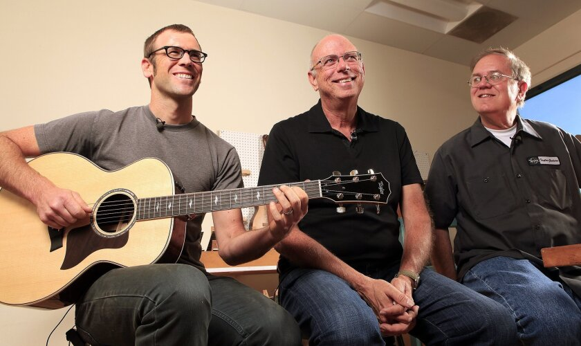 Taylor Guitars luthier Andy Powers (left), plays the soon-to-be released version of Taylor's new 800 series  guitar, alongside Taylor co-founders Bob Taylor (center) and Kurt Listug.