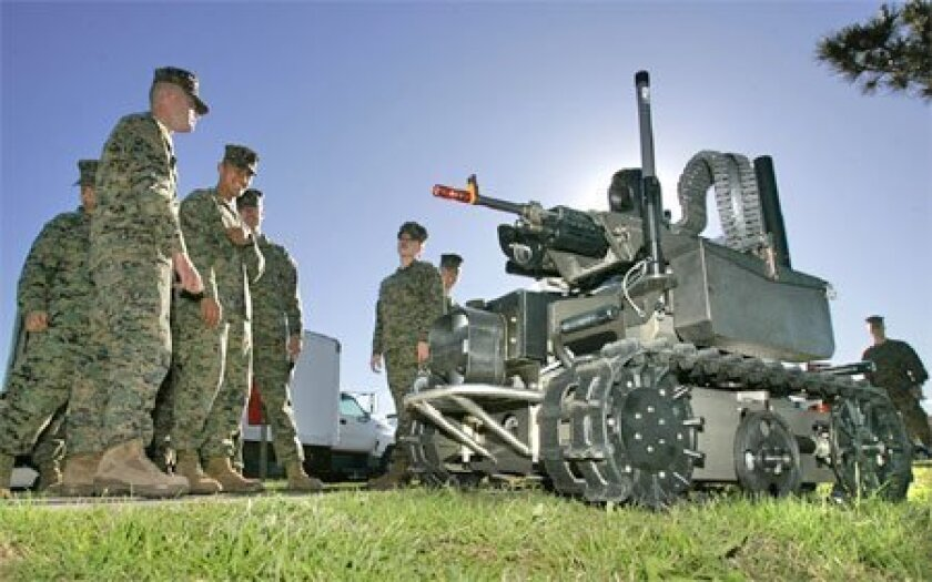 Camp Pendleton Marines watched at the Marine West Military Exposition  yesterday as a remote-controlled robot armed with 40 mm grenade launchers, a  machine gun and other attachments passed by. (Charlie Neuman / Union-Tribune)