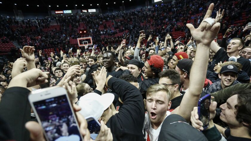 SDSU students celebrate after rushing the Viejas Arena court following the Aztecs' 65-57 win against No. 6 Nevada on Wednesday night.